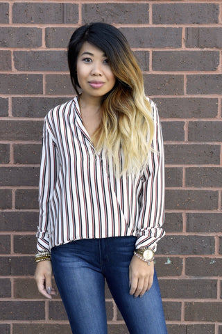 You'll look Like A Boss in this pretty blouse! The silky ivory top features retro-inspired stripes in brown and black with wrap over front, button and collar that will have you looking like the total boss babe you are whether its for work or play.