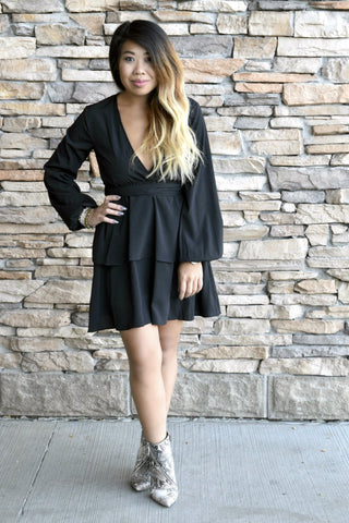 They'll all hope to See You There when you show up looking this good. This silky black dress is drop dead gorgeous with long, elastic hem sleeves, v-neckline, layered skirt and flattering fit and flare silhouette.