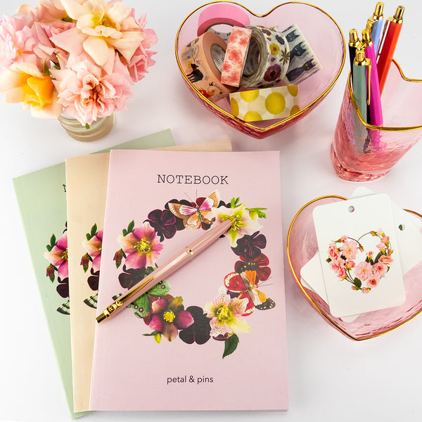notebooks featuring a flower garland design on a desk with heart shaped glass bowls filled with MT was tape, Ballograf pens in a rainbow of colours, gift tags with a heart designed in rose buds and a vase of garden roses.