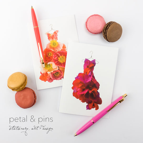 two greeting cards featuring images of dresses made from flowers by petal & pins styled with macarons and pens in orange and pink colours