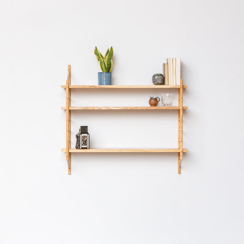 wall hung wooden shelving by John Eadon with shelves holding plants and books