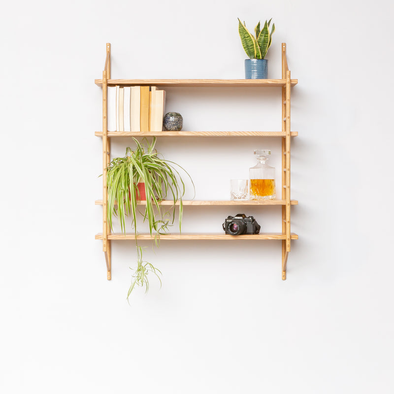wall hung wooden ladder shelving with four shelves holding plants and books and camera