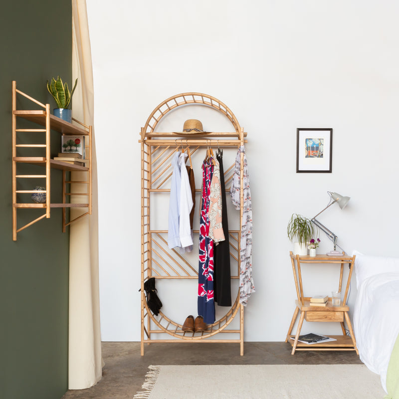 arched freestanding wooden ladder shelving by John Eadon used as wardrobe with matching wall hung ladder shelves