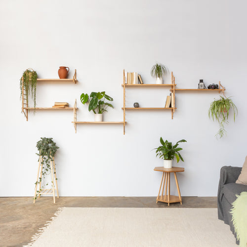 customised layout of wall hung wooden shelving by John Eadon