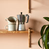 single wooden shelving with coffee mugs and mocha pot and plant