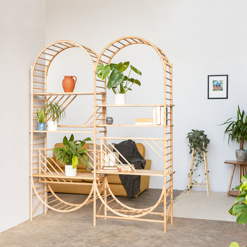 arched freestanding wooden ladder shelving by John Eadon double unit set used as a room divider with plants and books