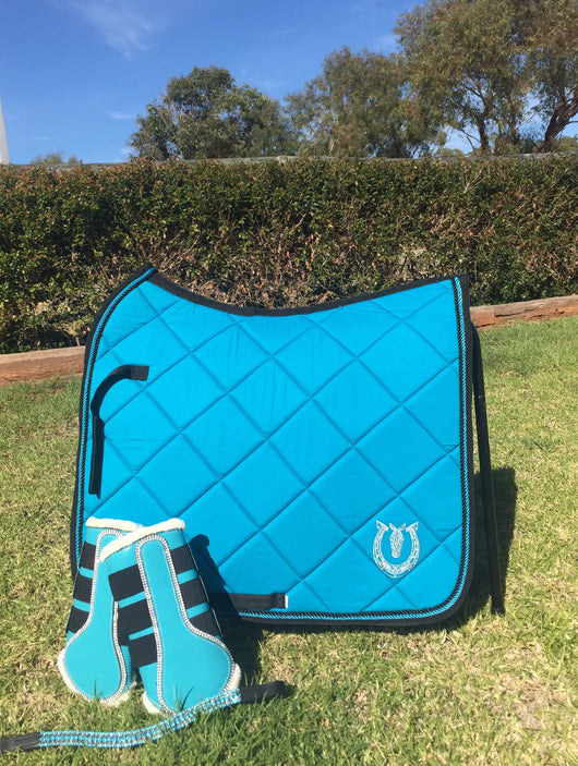 Turquoise dressage pad with black binding