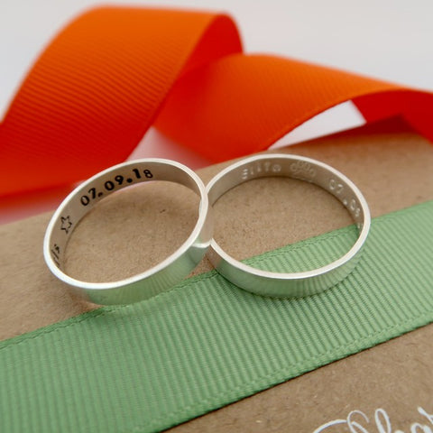 personalised silver couple rings each with different inscription