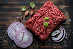 Large chunk of Lynch Farms raw ground beef surrounded by fresh herbs, spices and chopped onions