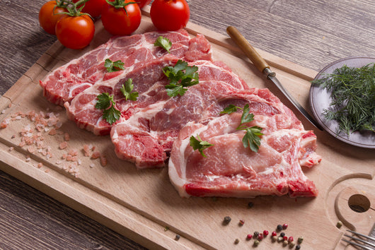 Four Lynch Farms raw pork chops on cutting board with tomatoes, parsley and black pepper