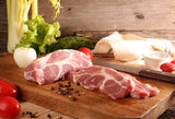 Lynch Farms raw pork steaks on cutting board surrounded by fresh vegetables and spices