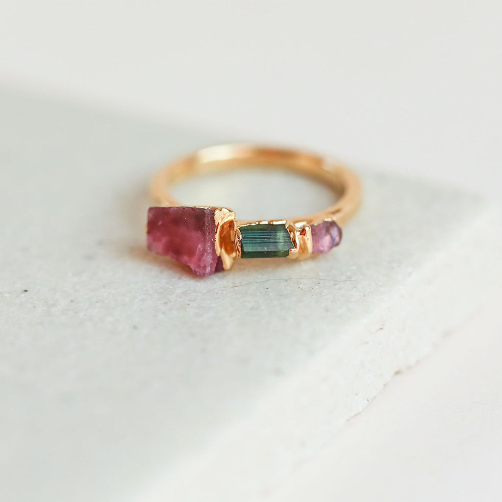 An epic tourmaline crystal ring featuring hot pink tourmaline, green tourmaline, and light pink tourmaline raw stones.