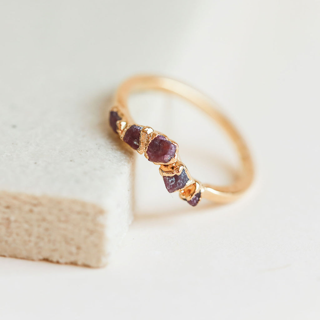 Delicate raw rubies give this curved ring a quiet edge.
