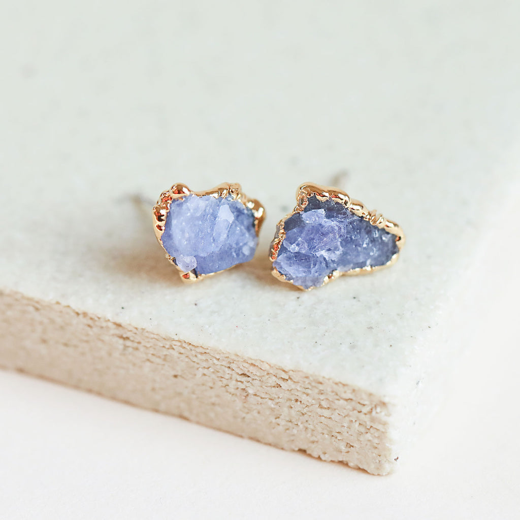 Raw tanzanite gemstones are encased in textured gold, and these tanzanite stud earrings