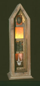 "Un-namable. wood, stone, thistle seeds, fern leaves, bone, light. 24″x7″x7,"" 2002"