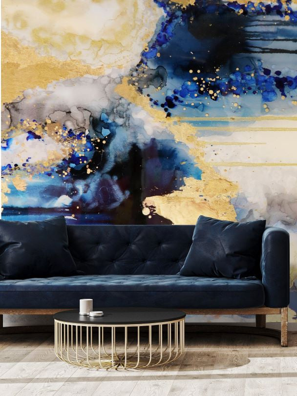 Abstract blue and gold wallpaper wall mural behind blue velvet sofa