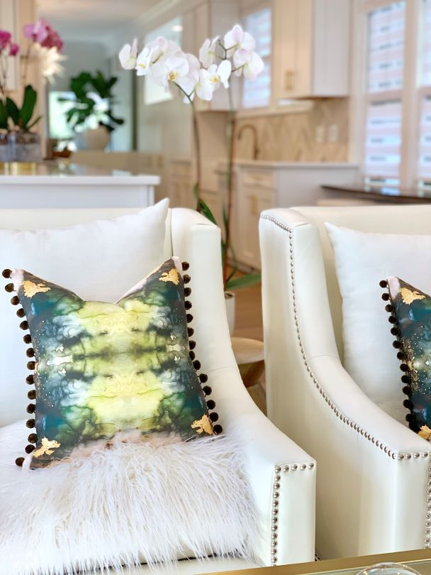 green jade pom pom textured pillow on a white fur chair