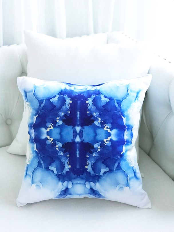 Blue designer pillow for sale on a white couch