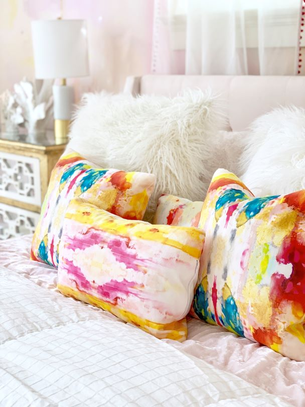 colorful throw pillow on white bedding with gold accents