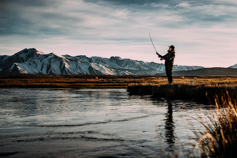 image of a man with a fishing rod and mountains behind him
