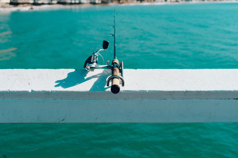 image of casting rod hanging over a wooden railing