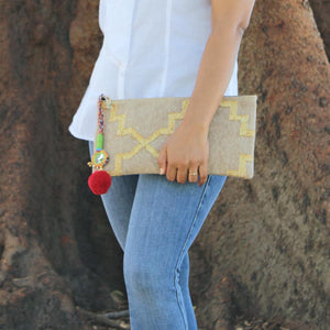 Model with bohemian gold dhurrie clutch