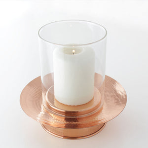 Copper hurricane lamp with a candle.