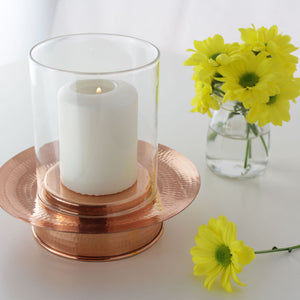 Copper hurricane lamp styled with a vase on side table