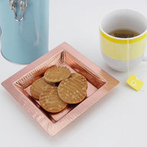 Square copper platter with cookies and a tea cup on the side.