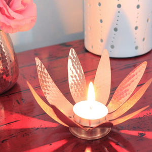 Sunflower copper tealight holder, styled next to a vase with flowers on red table
