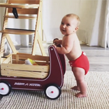 Baby pushing wagon in red modern cloth nappy