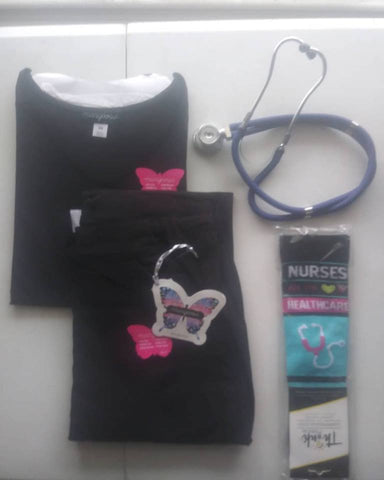 This is a Black scrub set from Mariposa by Koi fabric, nicely folded next to a pair of compression socks that say Nurse and a stethoscope.