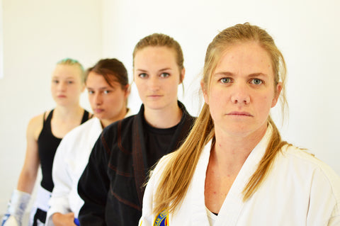 Four women standing in a line one in front of the other with serious looks on their faces. Each dressed in different martial arts uniforms.