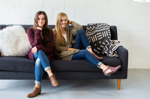 Two friends sitting on a a grey couch wearing cardigans and fall boots. Smiling and acting happy. One has her hand under her chin and one has her hand behind her head. White fur pillow and grey aztec blanket decorating the couch.