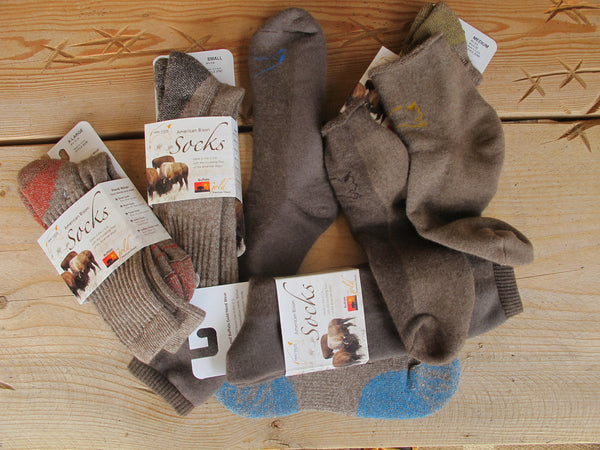 6 pair of bison wool socks on a wooden table