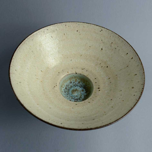Footed porcelain bowl with matte pale brown glaze by Peter Wills