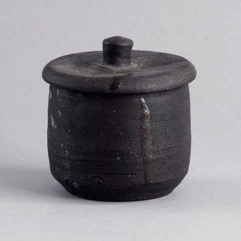 Stoneware lidded jar with matte black glaze by Janet Leach
