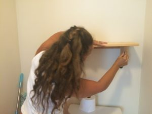 Me attempting to put up a shelf in the bathroom.
