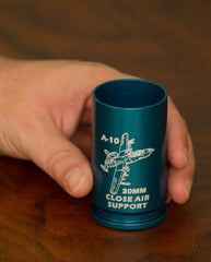 engraved 30mm shell casing shot glass in blue on hardwood table