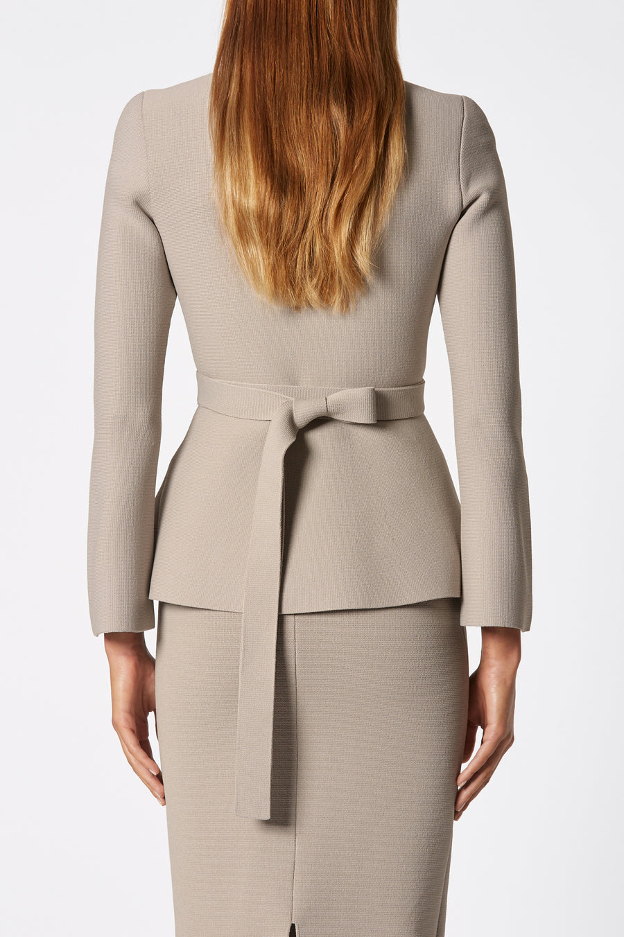 The Crepe Knit Ruffle Jacket is a tailored jacket that features a zip front, waist belt, and ruffled hem