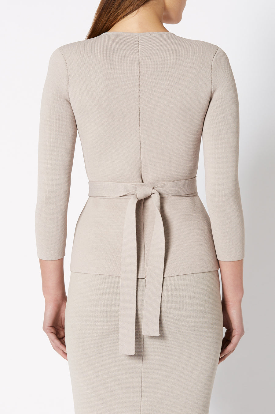 The Curved Hem Jacket closes at the front with a zip and includes a separate belt to be worn high around the waist.