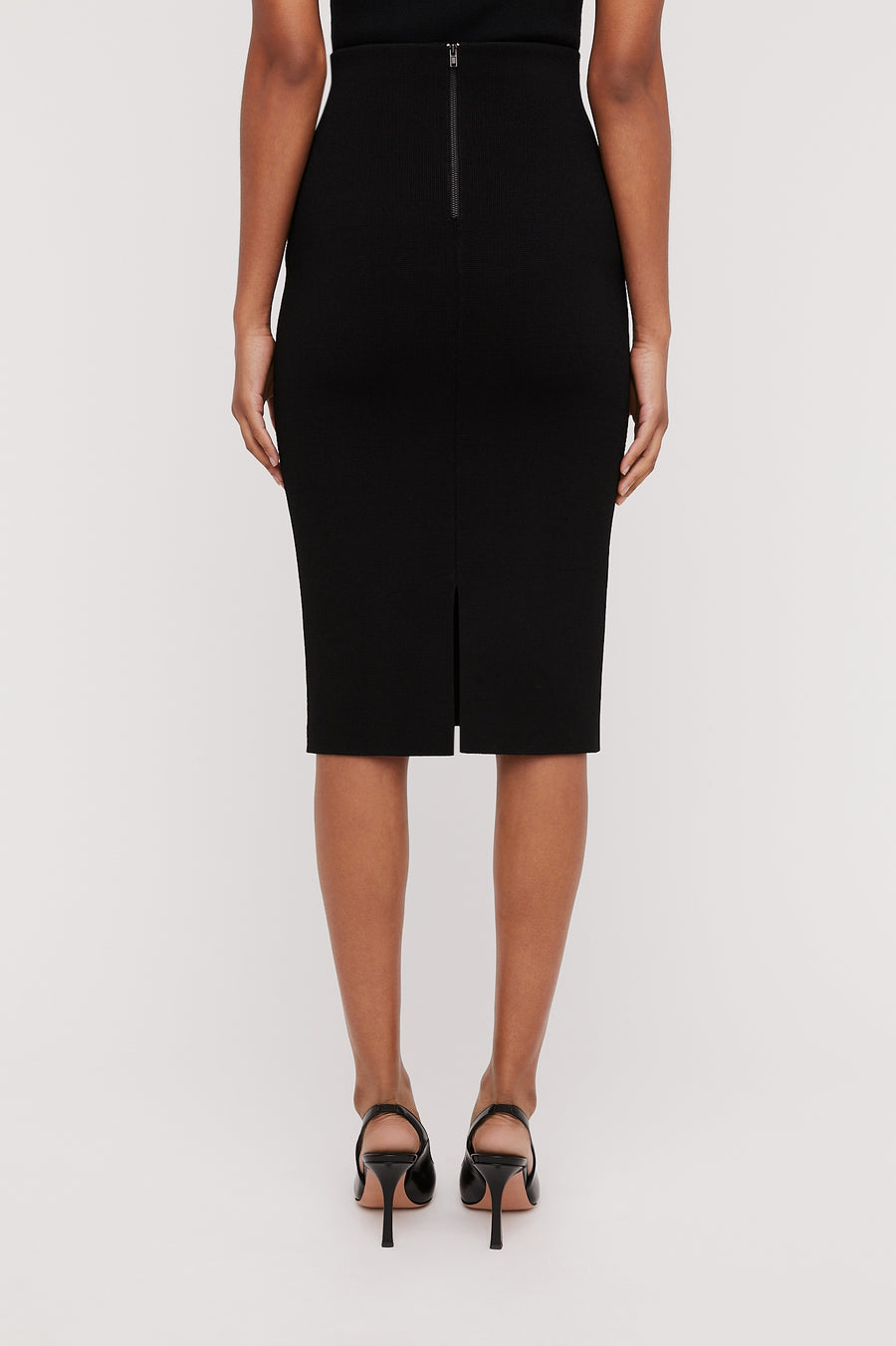 The Crepe Knit Slit Back Skirt is a tailored skirt. It is designed to sit high on the waist
