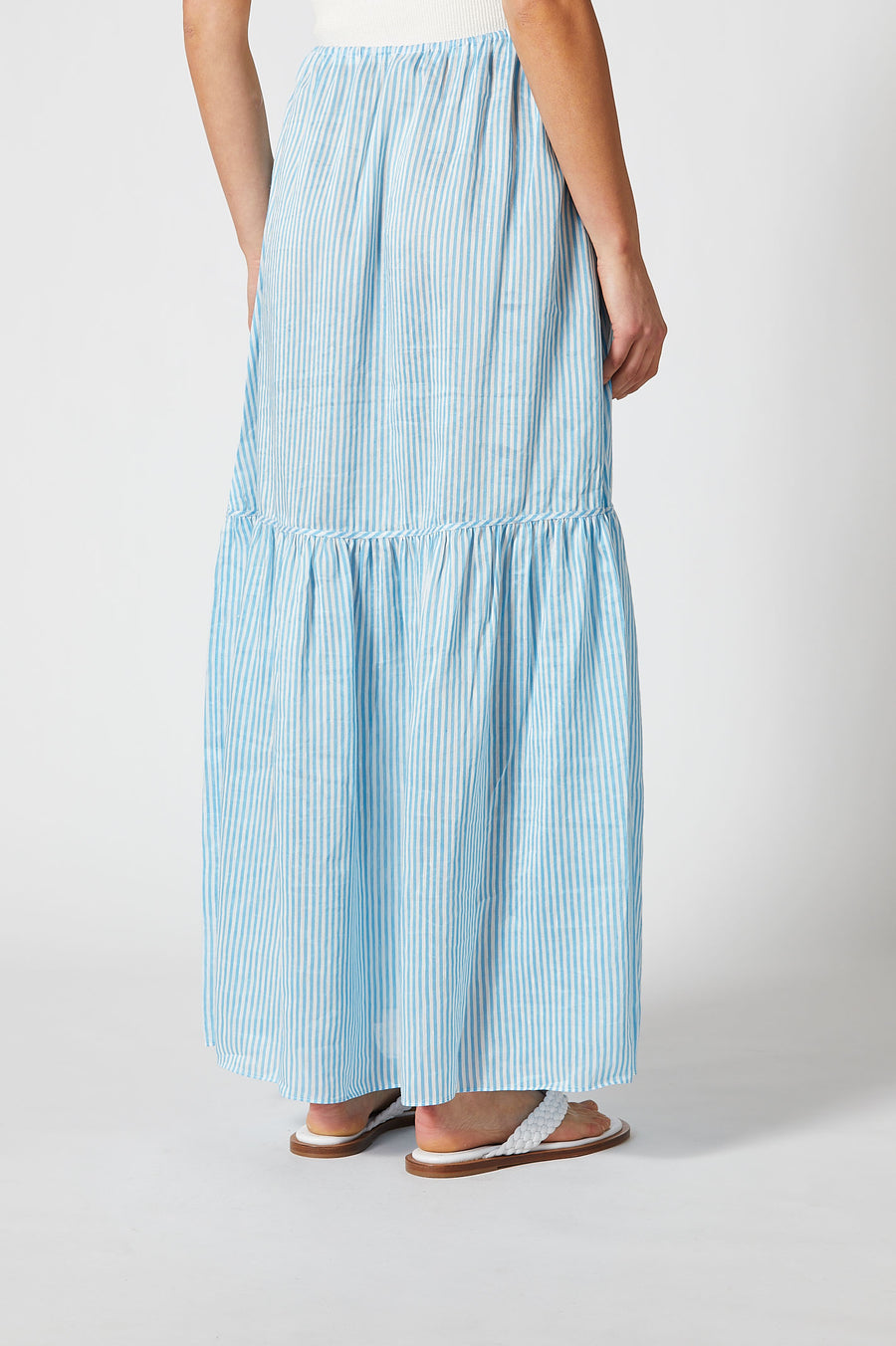 Crafted from a lightweight linen silk blend in a sky blue striped print, the  maxi skirt features a floaty, tired silhouette, concealed side pockets, and drawstring waist.