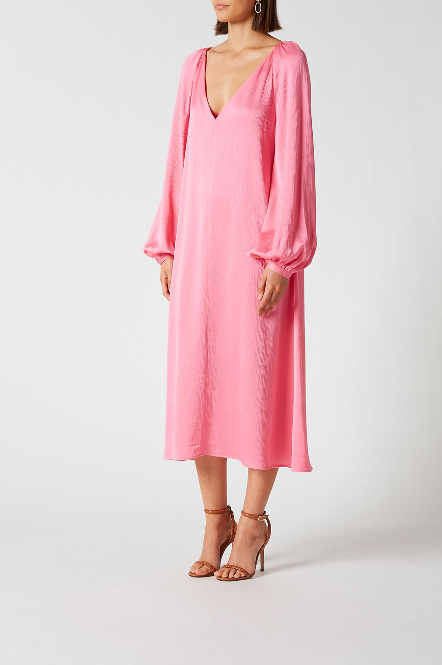 Cut from silk satin in an eye catching pink, the cocktail length dress features a deep v neckline and blouson sleeves.