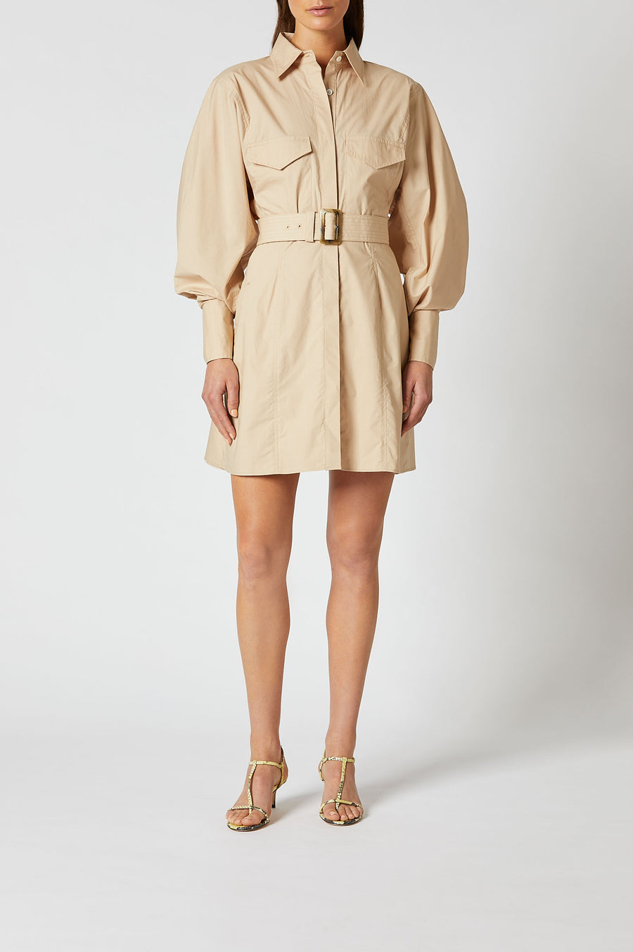 Featuring statement pocket details and exaggerated cuffs, the dress is cut to an A-line silhouette with long sleeves and front button closure.