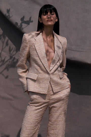 Crafted from cotton blend tweed, the pale pink single breasted silhouette features structured shoulders and a notch lapel.