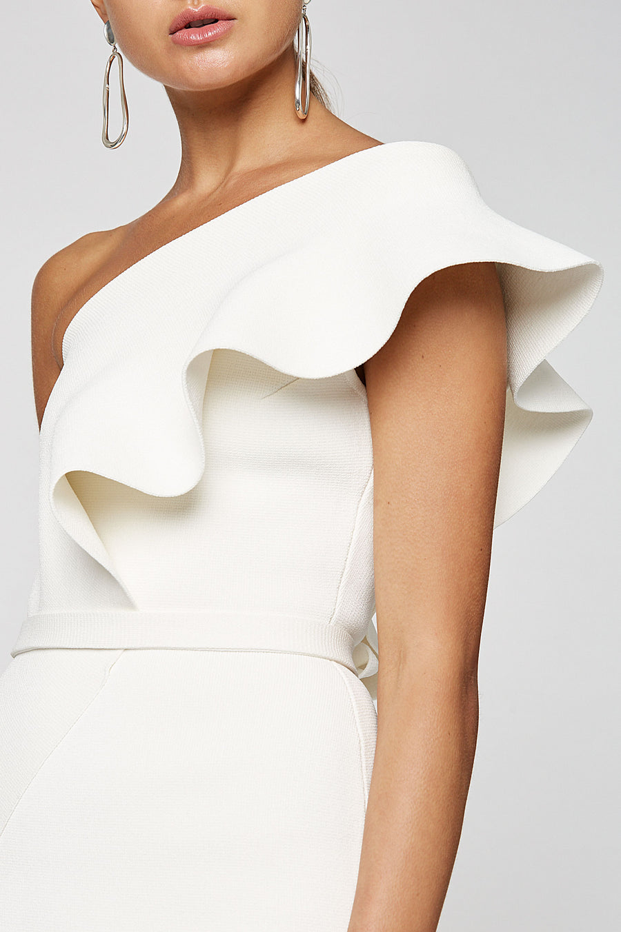 Crepe Knit Ruffle Dress, one shoulder dress, fitted throughout, ruffle feature from shoulder through opposite hip, falls just below knee, skirt has center back slit, Separate belt in same fabric included, Color Cream