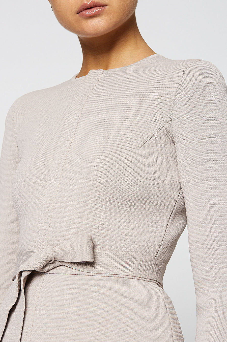 Crepe Knit Curved Hem Jacket, closes at the front with a zip, includes a separate belt, slim sleeve, round neckline, peplum style, Color Oyster