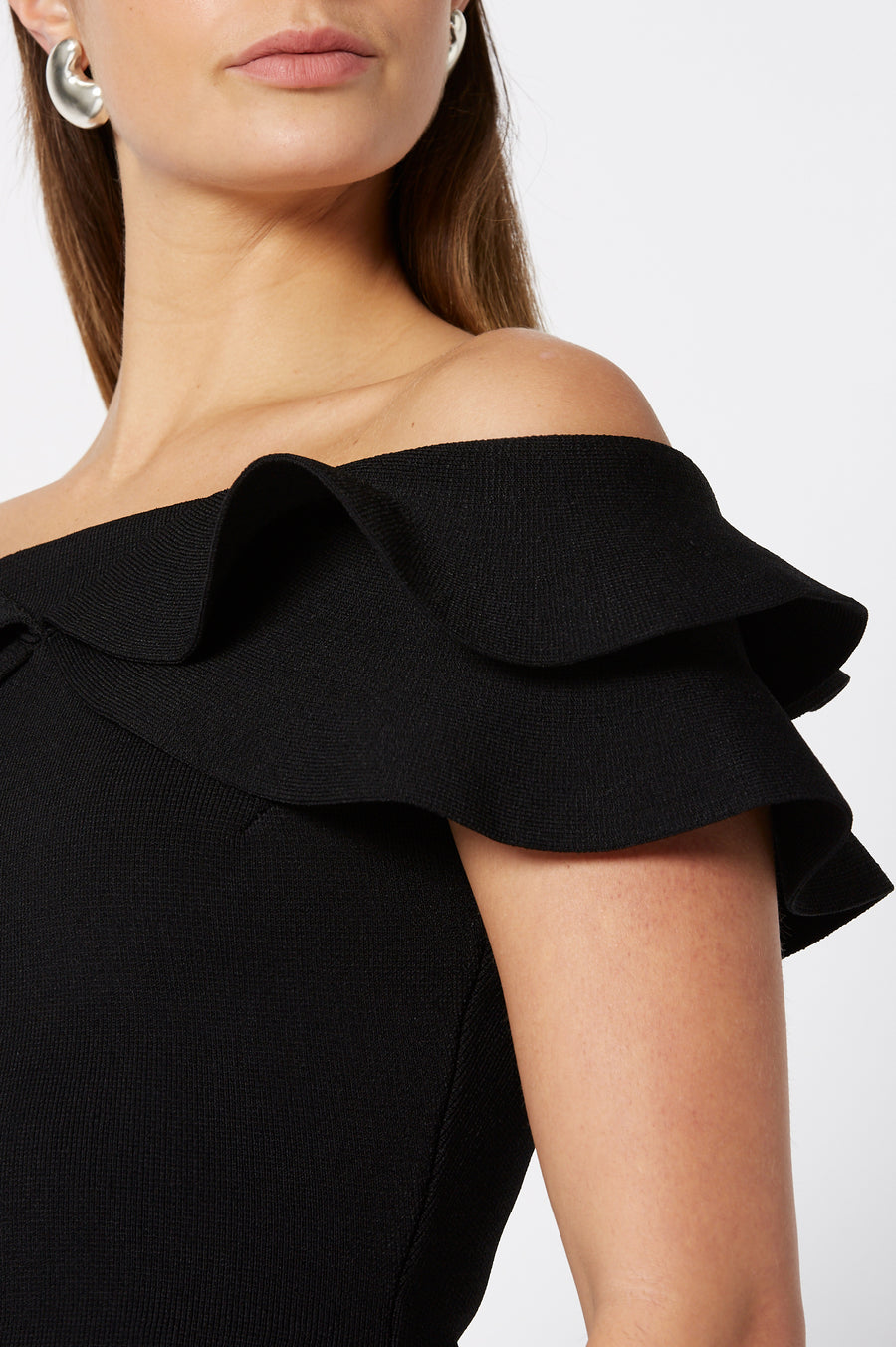 The Crepe Knit Cold Shoulder Ruffle Top is designed for a slim fit, color black
