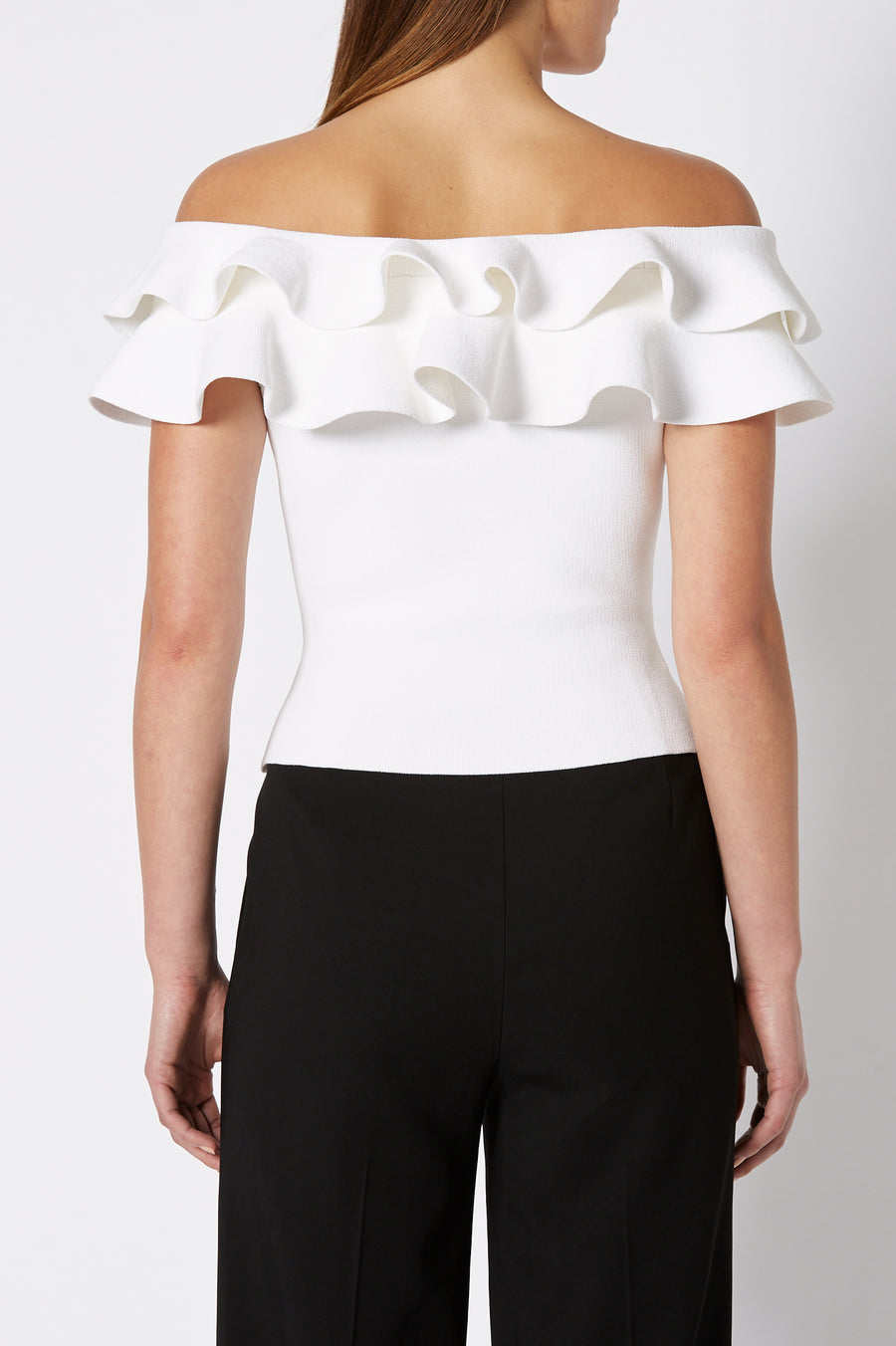 The Crepe Knit Cold Shoulder Ruffle Top is designed for a slim fit, color white